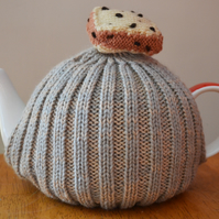 Small Handmade knitted tea cosy with a knitted piece of fruit cake on top