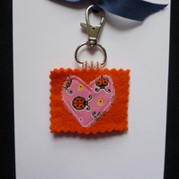 Orange wool felt keyring with ladybird applique