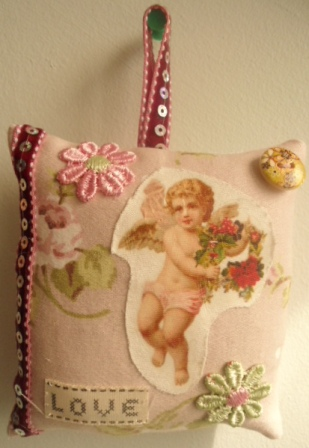 Sweet cherub rose-scented hanging pillow.
