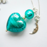 Deep green Murano glass heart pendant with silver charm and chain.