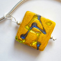 Decorated gold Murano glass pendant with sterling silver snake chain.