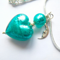 Murano glass green heart pendant with sterling silver charm and chain.