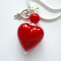 Red Murano glass heart pendant with sterling silver charm and chain.