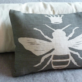 hand printed charcoal linen little queen bee cushion