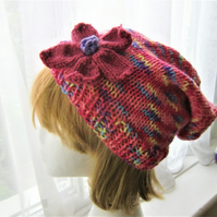 Colourful handknit slouchy hat with flower decoration