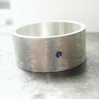 Large flat silver ring with a single blue sapphire , celebrate your love one