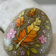 floating golden feathers - painted pebble