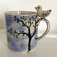 Half pint mug with tree design, blue sky and sculpted bird on the handle