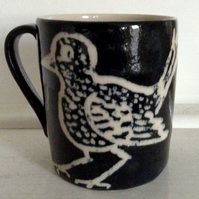 Mug in cream stoneware with black and cream bird decoration.