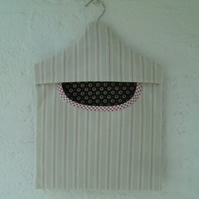 Peg bag in stripy canvas fabric with dark green lining and red trim.