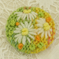 Daisy Brooch embroidered on knitted citrus background