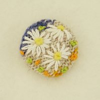 Daisy Brooch embroidered on knitted blue and cream background