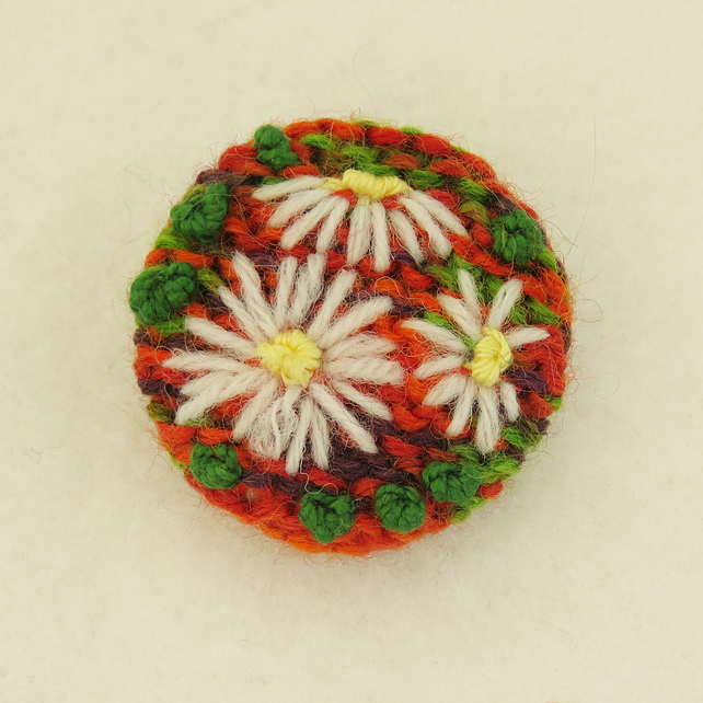 Daisy Brooch embroidered on knitted red, green and purple background