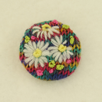 Daisy Brooch embroidered on knitted bright multi background