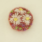 Daisy Brooch embroidered on knitted pink background