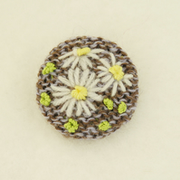 Daisy Brooch embroidered on knitted grey and beige background