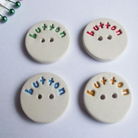 Set of four large ceramic buttons with the word button on the front