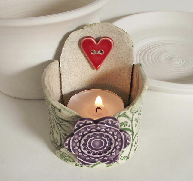Small ceramic tea light holder with heart and flower.