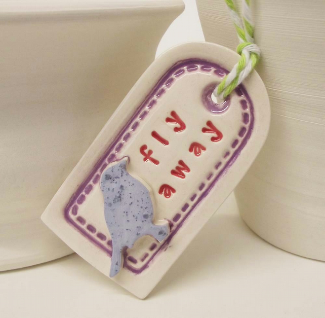 Small ceramic gift tag decoration with bird fly away