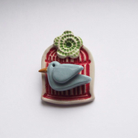 Little ceramic bird cage brooch with flower. Pottery jewellery