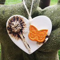 Pottery heart decoration with natural flower design and butterfly