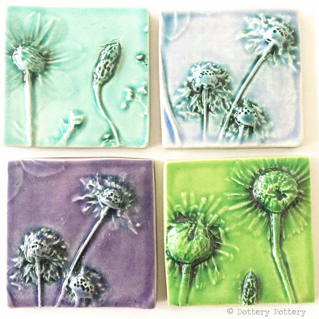 Set of four ceramic tiles with flower imprints and bright glazes purples, blues
