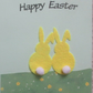 Easter Greeting Card - Two felt bunnies sitting on a hill of buttercups
