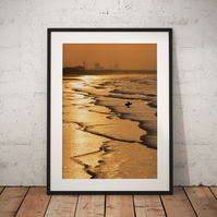 Saltburn photo showing a lone Surfer along a golden coastline during sunset