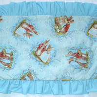 Beatrix Potter Mr and Mrs Bunny tossed on a turquoise pillow