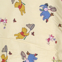 Winnie the Pooh, Eeyore, Tigger and Piglet on creamy  yellow cot quilt