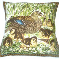 Mallard duck with her eight fluffy golden ducklings by the river bank cushion