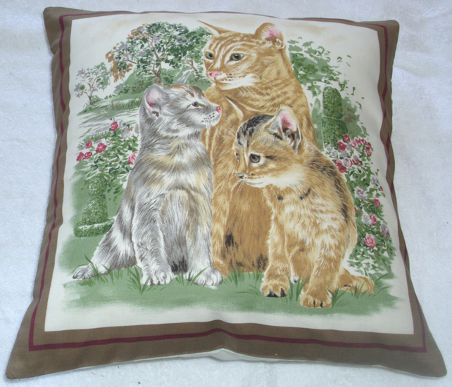 a lovely ginger cat and her two kittens in the garden cushion