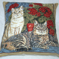 A ginger cat and tabby cat sitting in the window with pots of geraniums cushion