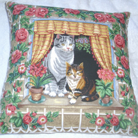 Lovely Grey Tabby cat and pretty tortoiseshell kitten sitting in window cushion