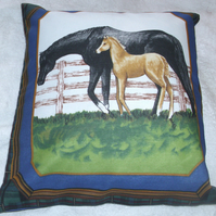A beautiful black mare and foal by a fence cushion
