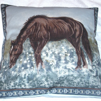 A beautiful brown horse grazing in a field cushion