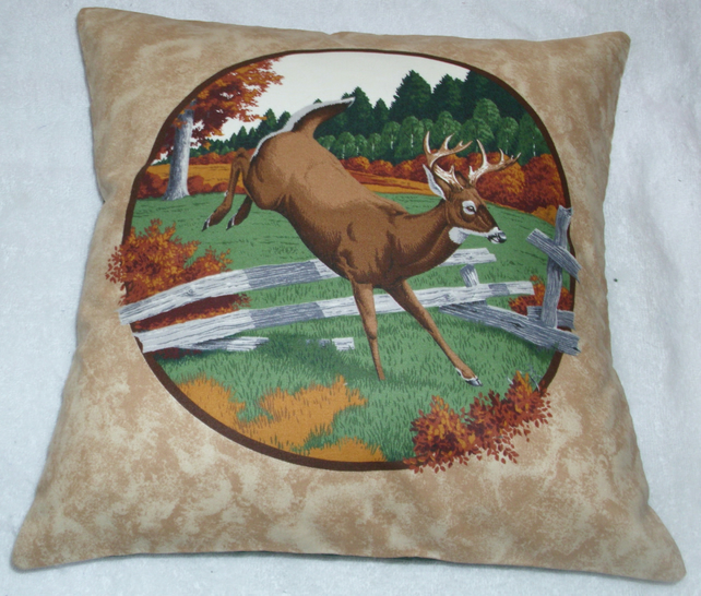 Stag leaping over a fence in a field by an Autumnal forest cushion