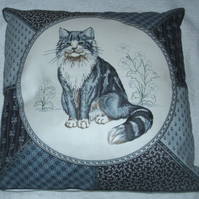 A very pretty grey and white fluffy cat cushion