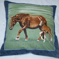 A beautiful brown horse and foal trotting across a field cushion