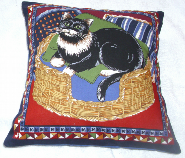 Lovely black and white cat sitting in a basket cushion
