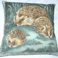 A Hedgehog and her two youngsters in a moonlit garden cushion