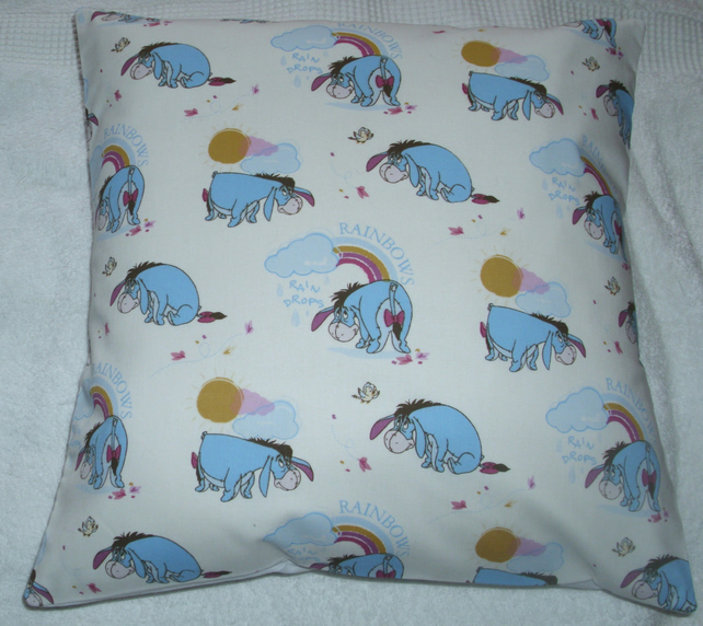 Eeyore sitting, standing, bending over looking at Rainbows cushion