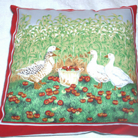 four geese in a corn field with lovely red apples in a pail cushion