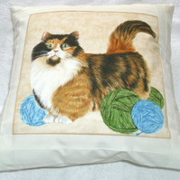 Pretty Tortoiseshell and white cat with balls of wool cushion