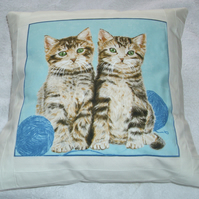Pretty tabby kittens with balls of wool cushion