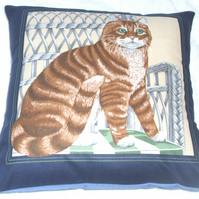 Lovely ginger Tabby cat sitting on a wickerwork chair cushion
