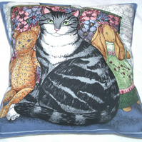 A very pretty grey and white Tabby cat with her toys cushion