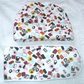 Liquorice Allsorts tossed on white tea cosy and ovengloves
