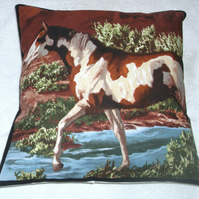 A beautiful brown  and white horse stepping through a stream cushion