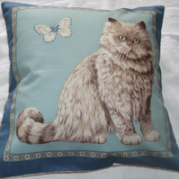 A very pretty grey and white fluffy cat sitting with butterfly cushion